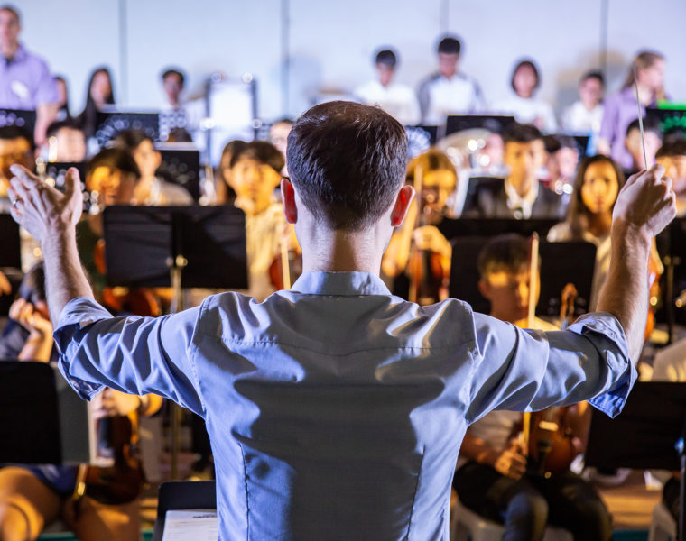 Male school conductor conductiong his student band